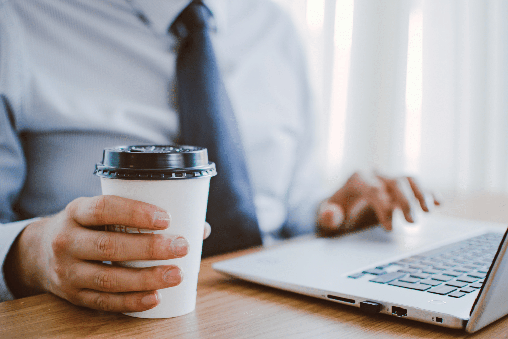 close up of hands using a laptop and drinking coffee