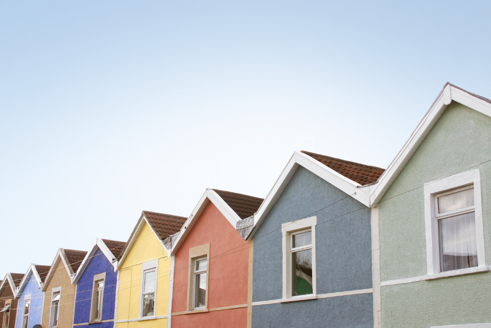 a row of colourful terraced houses with a blue sky behind them