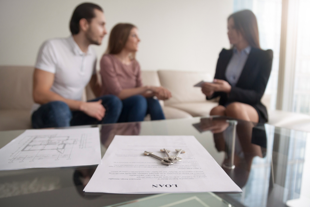 keys on a piece of paper, couple discussing with mortgage adviser in background