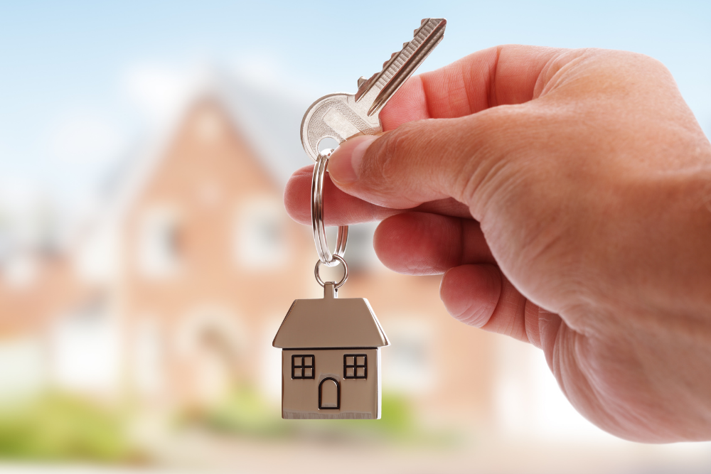 hand holding house keys with house keychain against blurred background