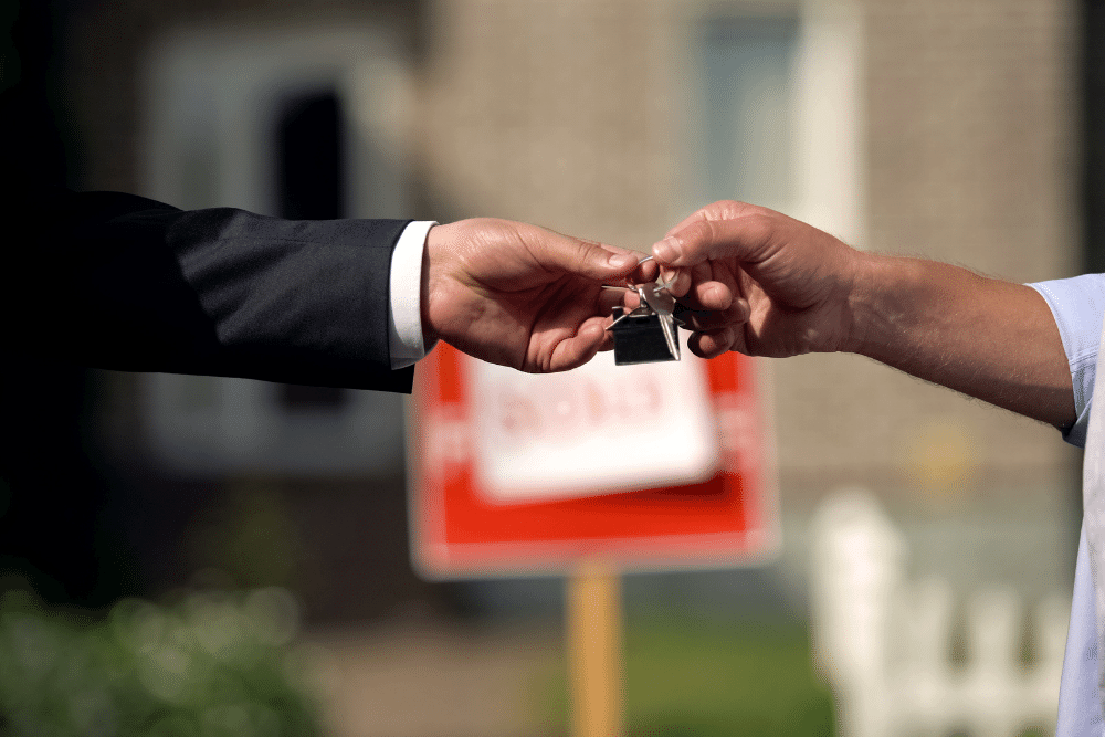 close up of hands as someone is given house keys with sold sign in background